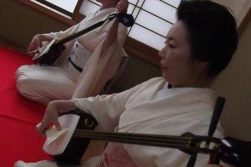 <p>Старшие гейши играют на своих сямисенах.</p>