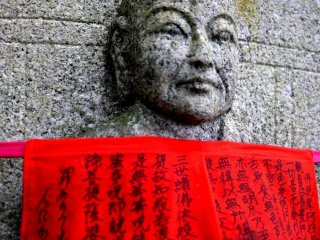 Sutras written on a statue's red apron