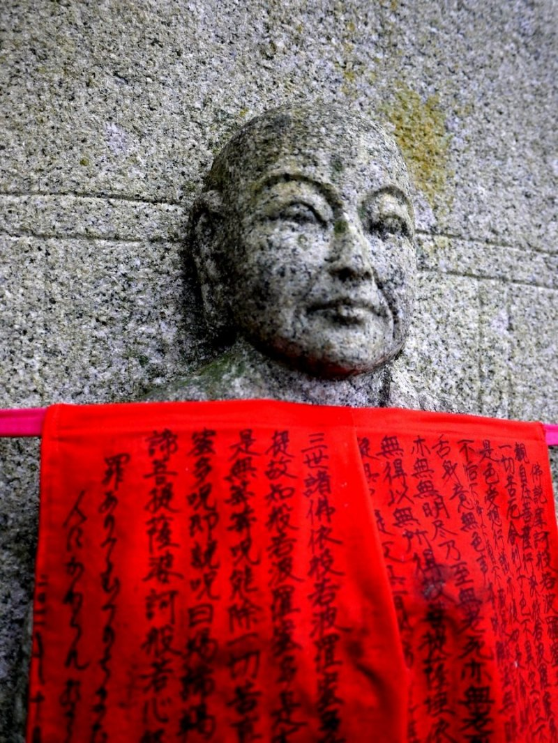 <p>Sutras written on a statue&#39;s red apron</p>