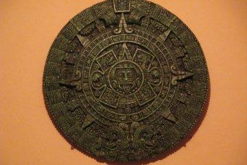 <p>The Aztec calendar&nbsp;hangs on the wall</p>