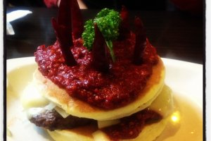 The Maestro: two pancakes stuffed with a hamburger, onions, and cheese, topped with chili sauce