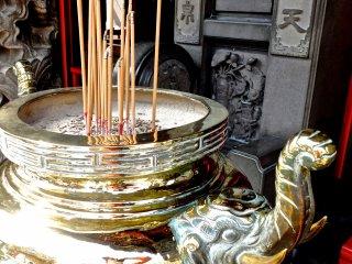 Recipiente de insenso de ouro com a forma de um elefante - Repare na escultura na parede no fundo