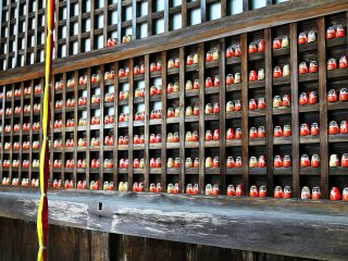 The deity is enshrined in framework filled with Daruma dolls. What could the meaning of the Daruma dolls being places in pairs mean?