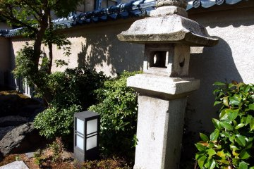 <p>Stone lantern standing alone in front of Three Sisters Shrine</p>