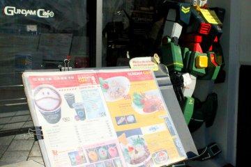 <p>A Gundam robot and a menu welcome each customer to their tiny food shop.</p>