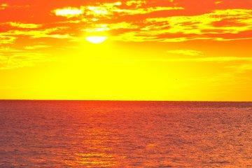 <p>เมื่อพระอาทิตย์ตกดินทิศตะวันตก ท้องฟ้าและน้ำทะเลเริ่มมีสีที่งดงาม</p>