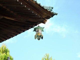 山門の屋根に掛かるブロンズ製の灯籠