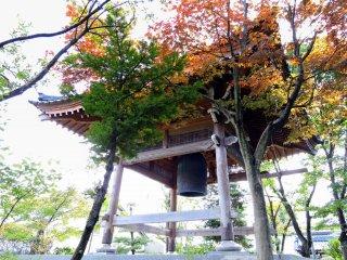 陽射しの中、紅葉に包まれる鐘楼