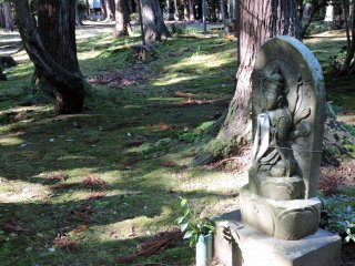 Statue Number six sits silently on the ground on which some brown leaves have fallen