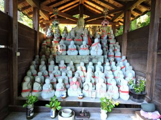 Rows of small jizo statues with the bigger one in the center at the top