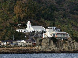 軍艦島への出航、神ノ島(左)とその中心部に建つ神ノ島教会 少し見づらいが船の航行を見守るかのように聖母マリア像が立つ