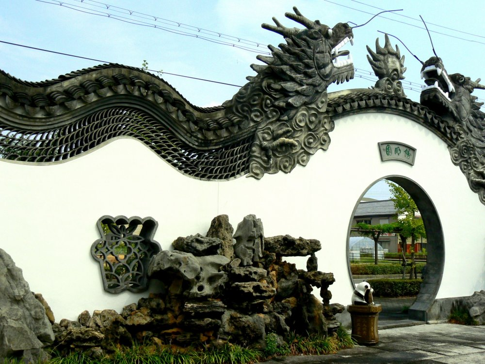 Magnificent dragons undulate along the top of the wall