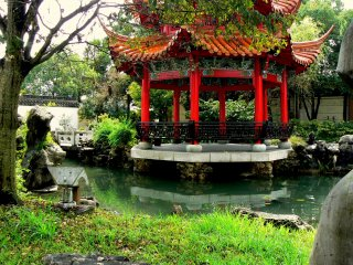 The pretty red pagoda rests on rocky pillars in the pond
