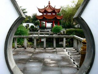 The pond and pagoda viewed through a vase-shaped window in the wall