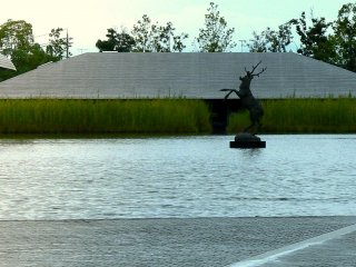 A prancing stag sculpture stands in the pond