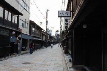 """신바시도리. 왼쪽이 기온 거리. 시중의 상가의 경관이 훌륭하다. 거리는 기온 신바시로서 전통적 건조물 보존지구로 지정되어 있어, 그 역사 원래는 지금의 야사카 신사의 몬젠마치로서 헤이안 중기경부터 발전해 카모가와히가시기시의 야마토 대로변에 야사카 신사의 참배객이나 연극객 상대의 찻집 거리가 만들어지게 되어, 그것들은 """"기온 소토 로쿠쵸""""라고 칭해졌다. 1732년이 되면, 막부보다 정식 찻집 영업의 허가가 나와, 새롭게 모토요시쵸, 하시모토쵸, 린카쵸, 스에요시쵸, 키요모토쵸, 토미나가쵸의 """"기온 나이 로쿠쵸""""가 개발되게 되었다. 현재의 기온 신바시는, 이 중의 모토요시쵸에 해당한다. 그리고, 에도시대 말기부터 메이지 시대 초기에 걸쳐 최성기를 맞이하여, 에도말기에는 500채나 되는 찻집이 기온에 있었다고 한다"""