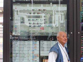 市バスの路線図の前に立つこの男性は「市バスコンシェルジュ」。市バスのことなら何でも、実に丁寧に教えてくれる。まず彼に聞いてみることだ