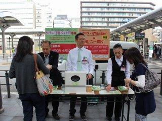 市バス会社スタッフが一日乗車券を販売している。京都観光に3回以上市バスを利用するプランを立てているのなら、一日乗車券¥500は安い