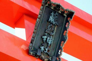 <p>Deep green signage of Fujishima Shrine hanging on the red torii gate</p>