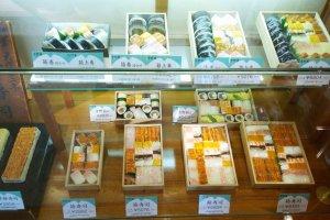รูปอาหารจำลองด้านหน้าร้านชั้นล่างที่โชว์ให้เห็นความหลากหลายของความอร่อยในสไตล์ซูชิกล่องของYoshino Sushi (吉野寿司)