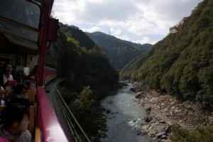 รถไฟสายโรแมนติกSagano Romantic Train กำลังวิ่งตามไล่เขาลัดเลาะไปตามหุบเขาและลำน้ำโฮะซึ (Hozugawa River) ซึ่งวิวทิวทัศน์ที่เห็นผ่านรถไฟนั้นงดงามมากตลอดเส้นทาง