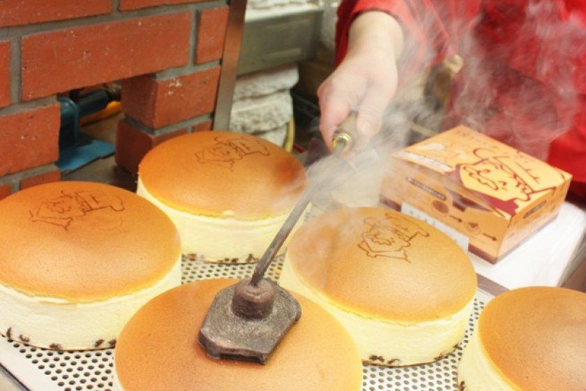 ชีสเค้กคุณลุง Rikuro Ojisan Cheesecake ร้อนๆ ที่เพิ่งออกจากเตาอบ ซึ่งพนักงานจะสั่นเสียงระฆังให้สัญญาณอันเป็นเอกลักษณ์ของชีสเค้กตำรับเก่าแก่นี้ และหลังจากนั้นพนักงานจะใช้ตราปั๊บเหล็กร้อนๆ ปั๊มโลโก้คุณลุงลงไปสดๆ ร้อนๆ บนชีสเค้กก่อนเสิร์ฟเรา เป็นความอร่อยอันหอมกรุ่นที่อยู่คู่โอซาก้ามานานเกือบกว่า 60 ปี เลยทีเดียว