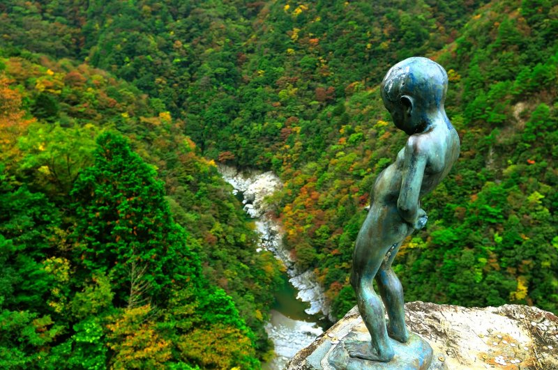 <p>He is peeing from the edge of a cliff! How audacious!</p>