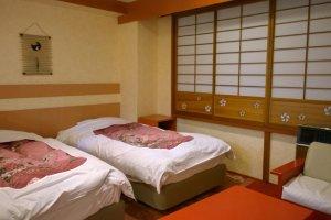 Kirakukan - เตียงนอนในกลิ่นอายญี่ปุ่นโบราณผสมผสานตะวันตกซึ่งจัดไว้เป็นอย่างดีริมหน้าต่างที่เห็นวิวอันงดงาม