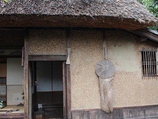 """The outside of the """"Hut of Fallen Persimmons"""". During the Edo period, the straw coat and hat hanging on the wall would have indicated whether the residents were home."""
