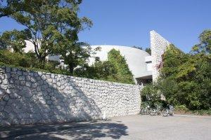 Benesse House Museum อันโดดเด่นบนยอดเขานี้เป็นพิพิธภัณฑ์ศิลปะแห่งแรกของเกาะและเป็นผู้เริ่มต้นสร้างสรรค์เกาะศิลปะแห่งนี้ให้เป็นที่รู้จักไปทั่วโลกมาตั้งแต่ปี ค.ศ.1989