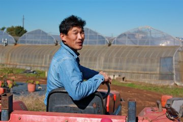 <p>Furito Yokota, part owner of Yokota Farm, takes a minute to answer questions the tour group has</p>