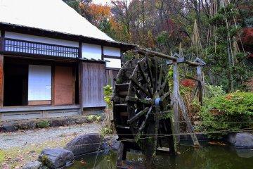 Водяная мельница в пруду. Тонкие нити, натянутые над прудом, призваны защитить карпов от птиц