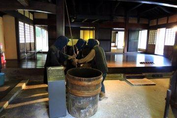Фигуры фермеров, обрабатывающих рис внутри дома