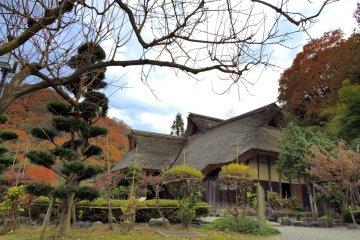 Вид на один из старых японских домов в деревне с деревьями сливы на переднем плане