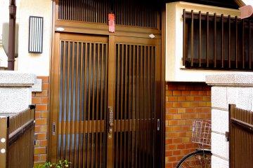 <p>숙소의 소박한 정문과 밖에 세워져 있는 자전거.</p>