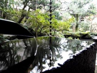 A chozubachi (water basin) at the garden's edge