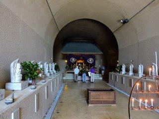 トンネルの突き当りに鎮座する本殿に参拝する人々