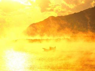 湧き立つ海霧に朝陽が斜めから射す