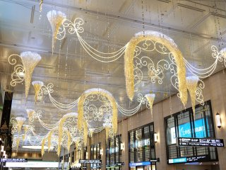 North-to-south concourse decorated with gold lights hanging from the ceiling along Hankyu Department Umeda Main Store