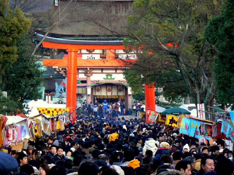 <p>People crowding under the big red torii</p>