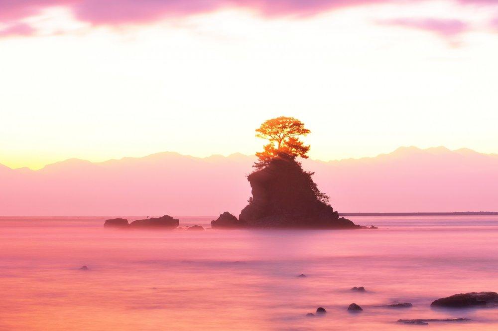Вид на пляж Амахараси в городе Хими, в префектуре Тояма. Остров в центре - Скала Йоситсунэ, в веливественной горой Татэяма на заднем плане.