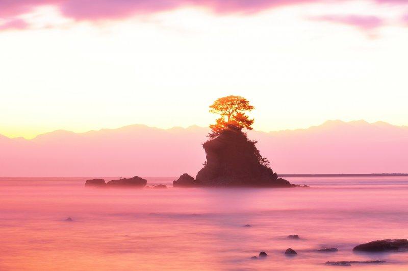 Vista de la playa Amaharashi en la ciudad de Himi en la prefectura de Toyama. La isla en el centro es 'Yoshitsune Rock' con la majestuosa cordillera de la Montaña Tateyama al fondo.