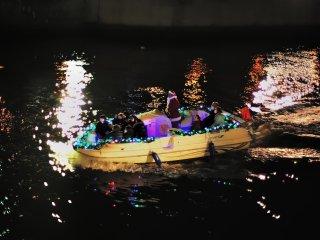 Illuminated boat floating on Dojima River going under Yodoyabashi and Ooebashi Bridges