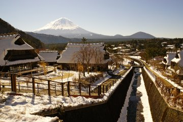 <p>One of the many magical views of Mt. Fuji and the traditional thatched roof houses from Fujimi Bridge</p>
