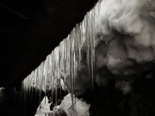 On a village house trapped in snow, icicles sparkle as they catch the light - nature's artwork!