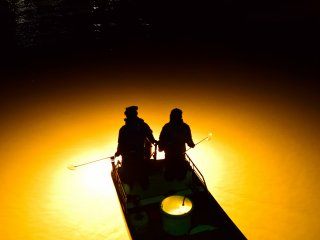 Silhouettes of the fishermen float on the beam of light spread over the river (Shinmachi River)