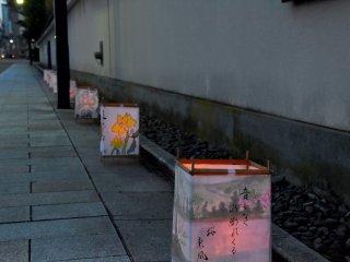 Lanternas artesanais colocadas ao longo da estrada em frente do Yokokan