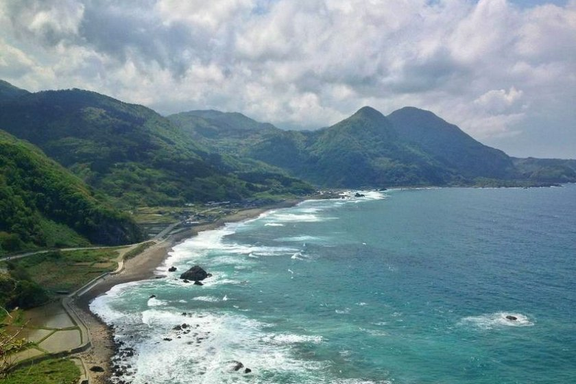 From this distance, the dramatic scenery of forest-covered mountains and wild, white-capped waves overshadows the small cluster of buildings in Iwayaguchi.