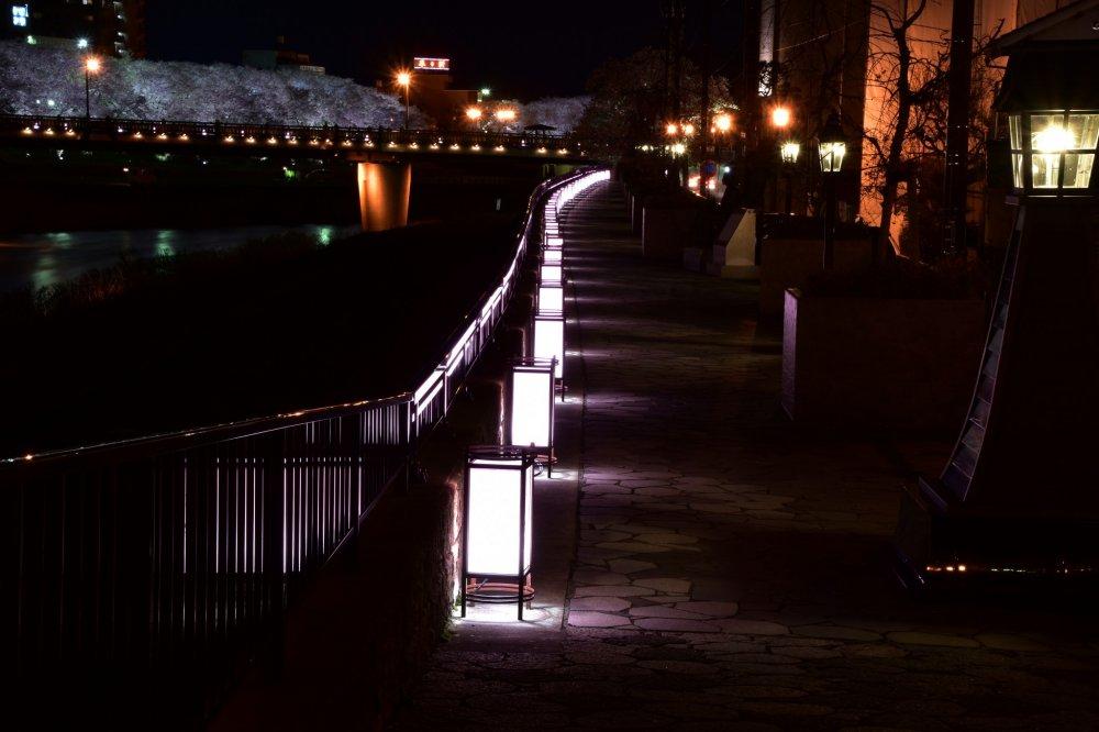 Lanternas em papel iluminam delicadamente o pavimento em pedra do passeio do rio Asuwa