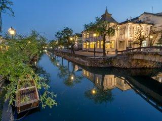 Le ciel bleu à l'heure bleue créé de magnifiques reflets dans le canal du quartier historique Kurashiki Bikan